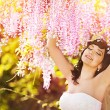 Beautiful bride in a rain of pink flowers — Stock Photo