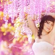Beautiful bride in a rain of pink flowers — Stock Photo #27489187