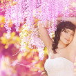 Beautiful bride in a rain of pink flowers — Stock Photo #27489851