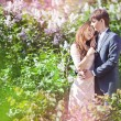 Passionate couple in a park of blossoming lilac — Stock Photo