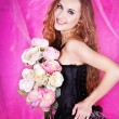 Beautiful woman in black corset with bouquet of flowers — Стоковая фотография