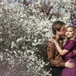 Happy young couple in a park of cherry blossom — Stock Photo #27492149