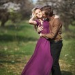 Happy young couple in a park of cherry blossom — Stock Photo #27492275