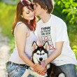 A young couple walking a dog — Stock Photo #27492587