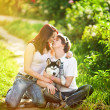 A young couple walking a dog — Stock Photo #27492597