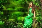 Красивая девушка в зеленом платье в сказочном лесу — Стоковое фото