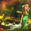 Beautiful girl in green dress in the forest pond — Stock Photo #28560383