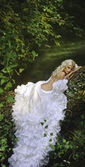 Blonde bride angel in long white skirt standing in forest — Stock Photo