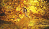 Beautiful girl in a yellow dress walking the air in the forest — Stockfoto
