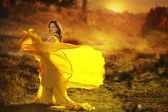 Beautiful girl in a yellow dress walking the air in the forest — Zdjęcie stockowe