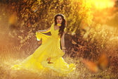 Beautiful girl in a yellow dress walking the air in the forest — Foto Stock