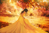 Beautiful girl in a yellow dress walking the air in the forest — Photo