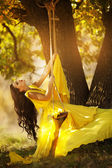 Beautiful girl in a yellow dress riding on a swing — Stock Photo