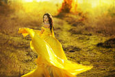 Beautiful girl in a yellow dress air — Стоковое фото