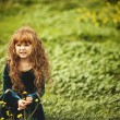Beautiful girl with red hair on a green glade — Stock Photo