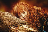Portrait of a pretty young girl lying on a tree branch — Foto Stock
