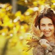 Happy young teen girl in autumn scenery throwing leaves — Stock Photo