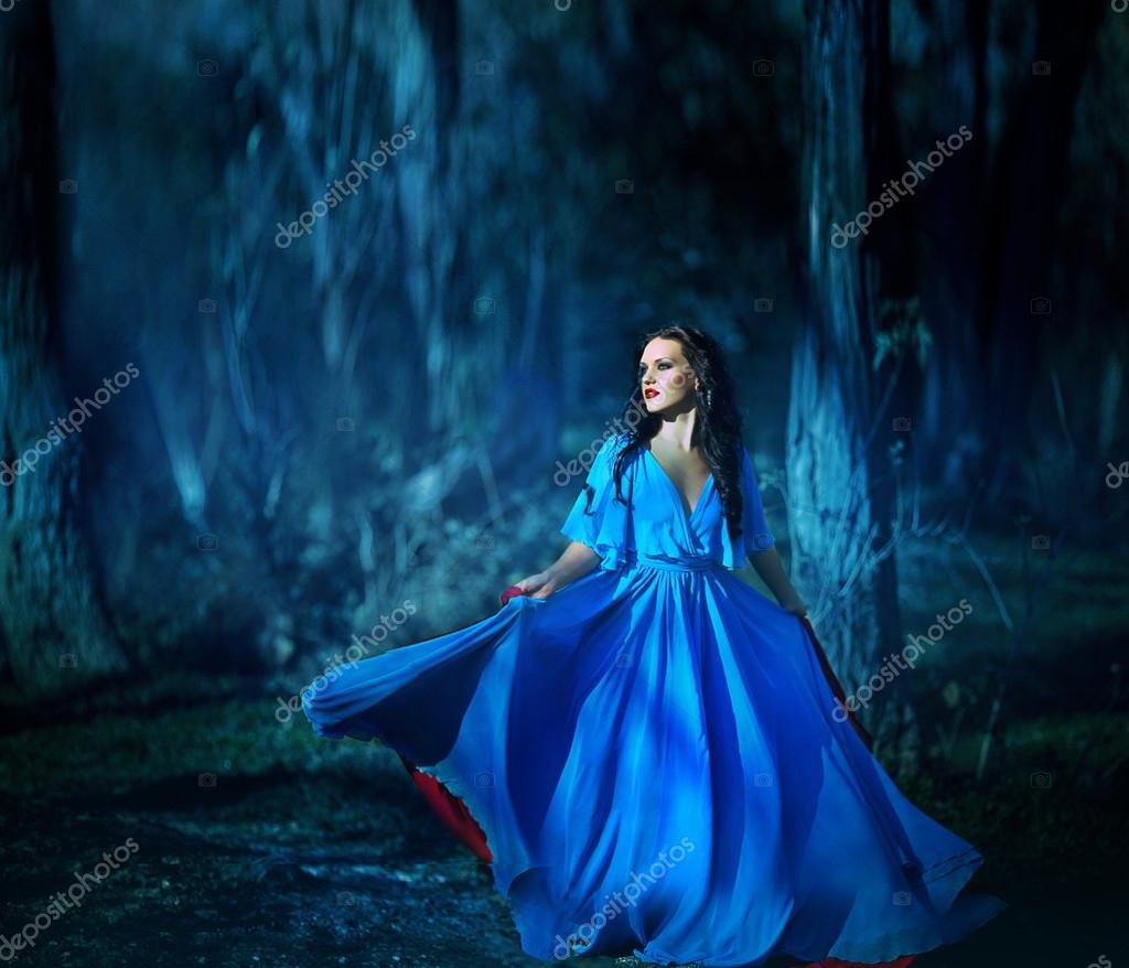 Beautiful girl in blue dress walking in the magical forest — Stock ...