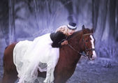 Beautiful blonde girl in white dress on a horse — Stockfoto