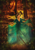 Beautiful girl in blue dress walking in the magical forest — Stock Photo