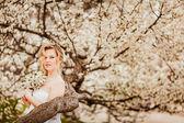 Beautiful blond girl in blossom garden — Stock Photo