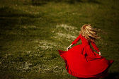Beautiful blonde in a red dress dancing on green meadow — Stock Photo