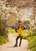 Cute little girl in a red hat posing near blooming trees in the park — Stock Photo