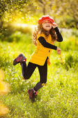 Happy little girl in a red hat having fun outdoors in park — Stock Photo