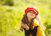 Sevimli küçük bir kız açık havada bir parkta kırmızı şapkalı bir bahar portresi — Stok fotoğraf