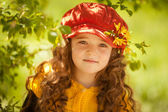 Spring portrait of a cute little girl in a red hat outdoors in a park — Stock Photo