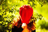 Cute little girl covered her face with a red hat — Stock Photo