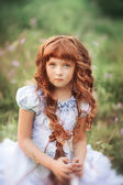 Little  girl sitting on the grass — Stock Photo