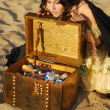 Girl on the beach with a chest of treasures — Stock Photo #9596469