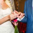 The bride wears the ring to the groom at a wedding - Stock Photo
