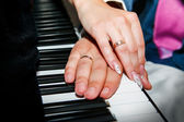 Hands of bride and groom at the piano — Stock Photo