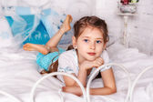 Beautiful little girl sits on white blanket in her bedroom — Stock Photo