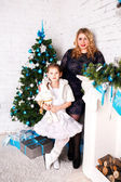 Young mother and her daughter by a fireplace on Christmas — Stock Photo