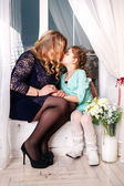 Mother and little daughter with flowers. Close Up Of Affectionate Mother And Daughter At Home — Stok fotoğraf