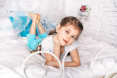 Beautiful little girl sits on white blanket in her bedroom — Stockfoto
