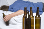 Man passed out with a beer bottle in his hand — Stock Photo