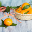 One mandarin near the basket with other mandarins. Roll of tape on the background — Stock Photo