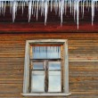 Icicles on the roof of a wooden house with windows — Stock Photo #22162389