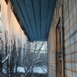 Icicles on the roof of a wooden house with windows - Stock Photo
