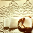 Gold wedding rings on white pillow - Stock Photo