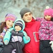 Complete family with children walking in winter — Stock Photo #22168055