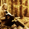 Young beautiful girl with a book in the autumn forest — Stock Photo