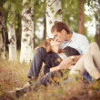 Embracing and kissing young guy and girl on nature — Stock Photo