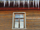 Icicles on the roof of a wooden house with windows — Stok fotoğraf