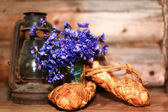 Antique oil lamp and blue flowers — Stock Photo