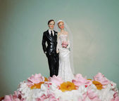 Figurines of the bride and groom on a wedding cake — Photo